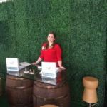 CERF employee promoting Rental Catalog on Wine Barrel Table with Wine Cork Stools and Hedge Backdrop