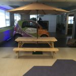 Picnic Table and Patio Umbrella in front of Smart Car
